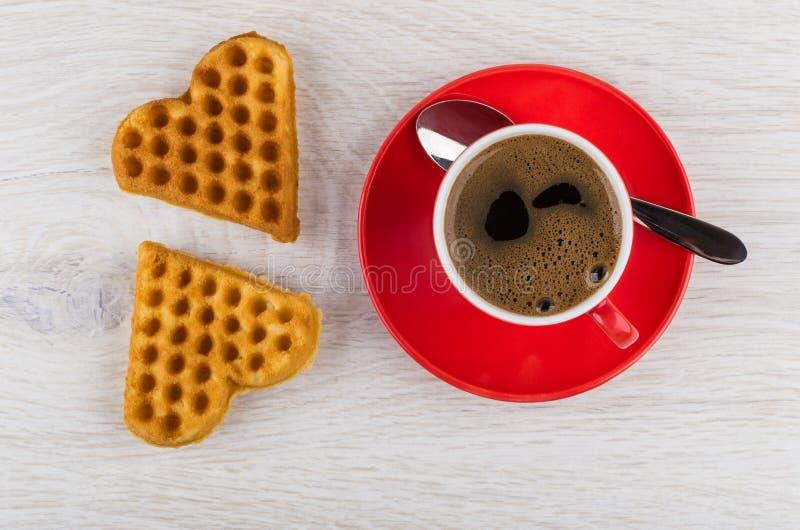 Zwarte koffie in rode kop, lepel op schotel, koekjes stock foto