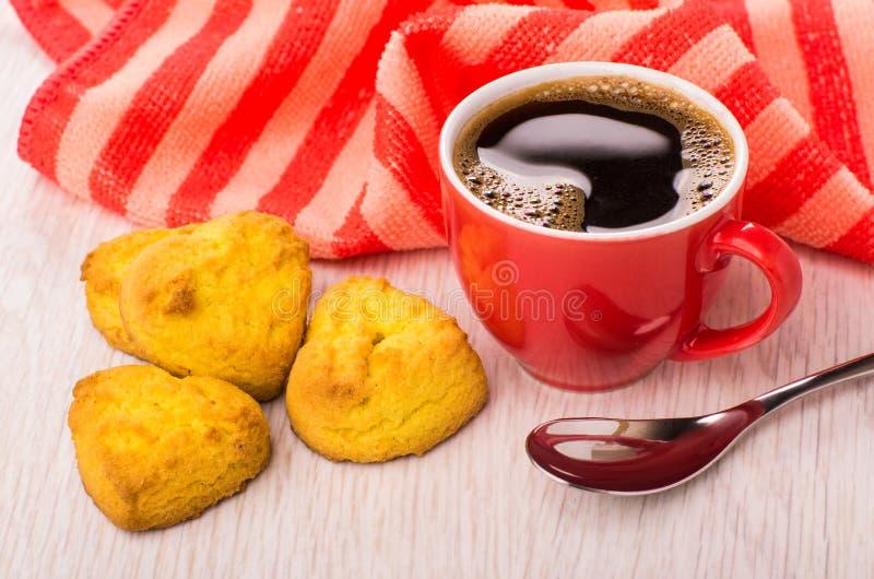 Zwarte koffie in rode kop, servet, lepel, koekjes stock foto's