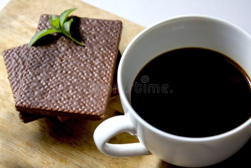 Zwarte koffie in witte glas en Wafeltjechocolade stock afbeeldingen