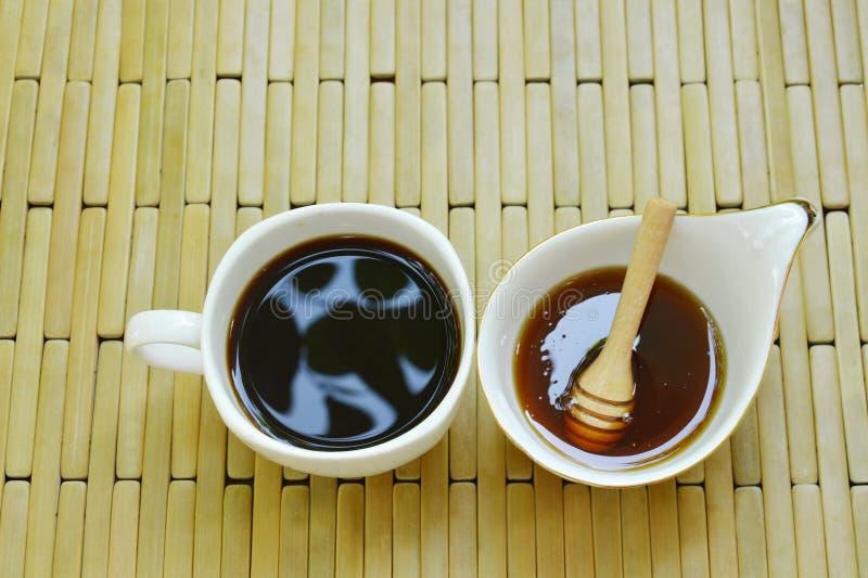 Zwarte koffiekop en honing met houten lepel op bamboeachtergrond royalty-vrije stock afbeelding