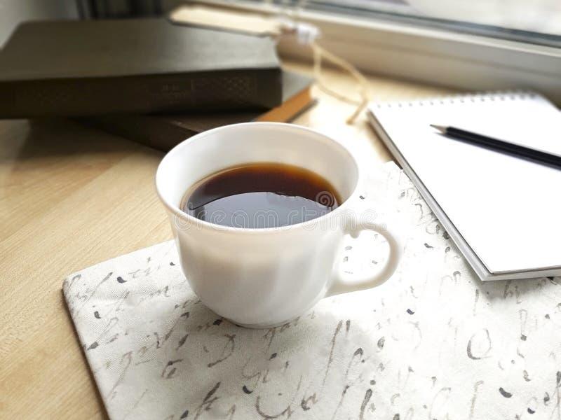 Zwarte koffiekop, lege blocnote en boeken op lijst stock foto's