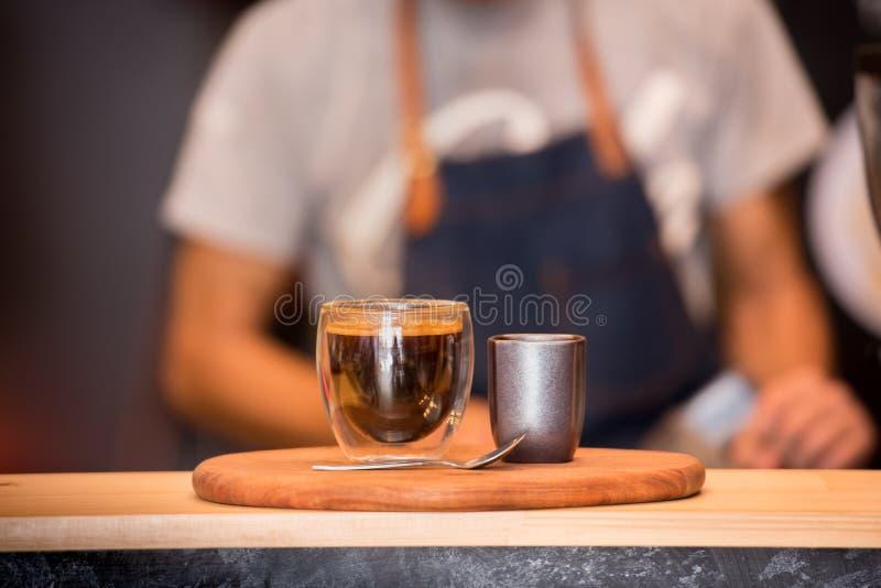Zwarte Koffiekop op Houten Lijst en Koffie Barista Horizontal en Vage Achtergrond met Filmeffect Het knappe barista voorbereiding stock foto's