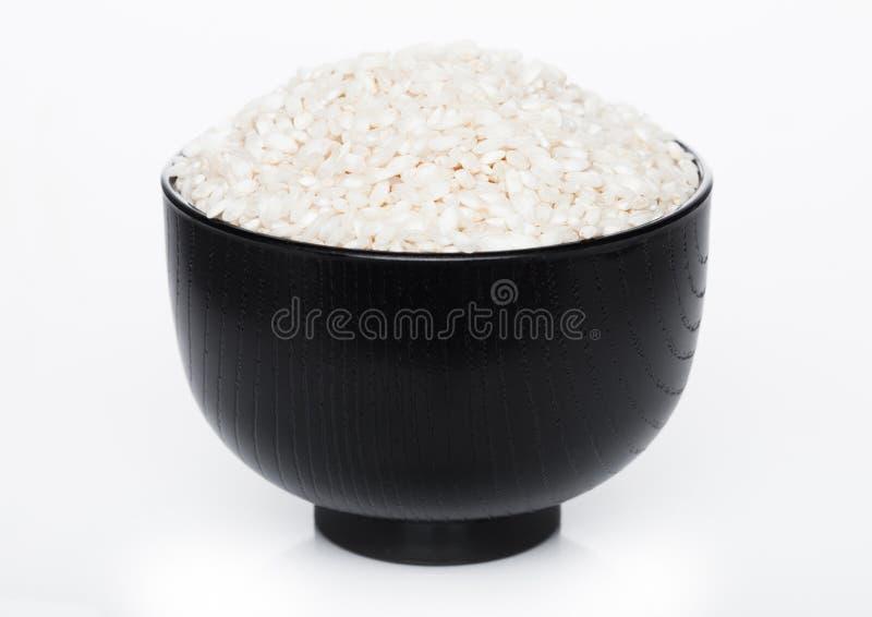 Zwarte kom de ruwe organische rijst van arboriorisotto op witte achtergrond Gezond voedsel royalty-vrije stock foto