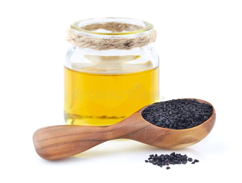 Zwarte komijnolie met zaden stock foto's
