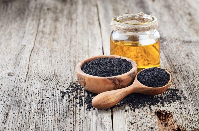 Zwarte komijnolie met zaden stock afbeeldingen