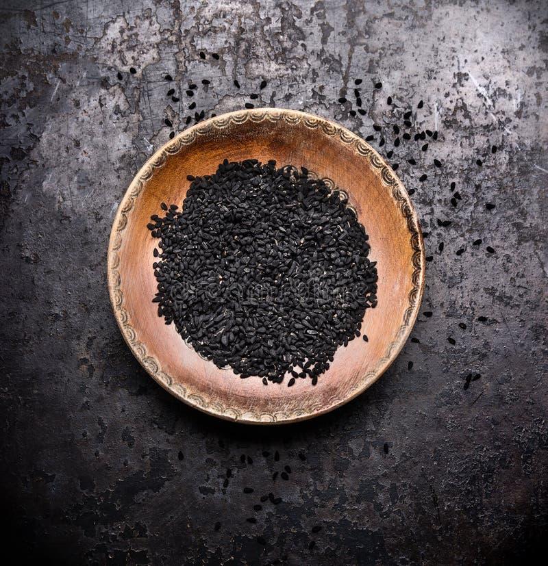 Zwarte komijnzaden in rustieke kom op donkere uitstekende achtergrond, hoogste mening royalty-vrije stock foto's
