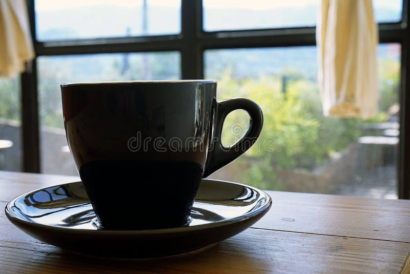Zwarte kop met het stomen van hete koffie op de houten lijst met vage groene tuinachtergrond royalty-vrije stock afbeelding