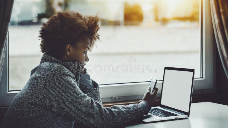 Zwarte krullende freelancer met laptop en smartphone royalty-vrije stock foto
