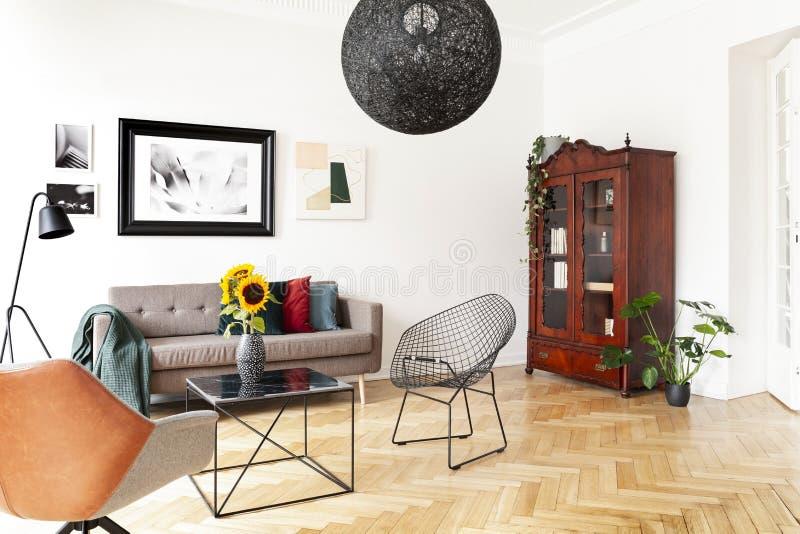 Zwarte lamp boven leunstoel en lijst in helder woonkamerbinnenland met affiche en installaties Echte foto stock fotografie