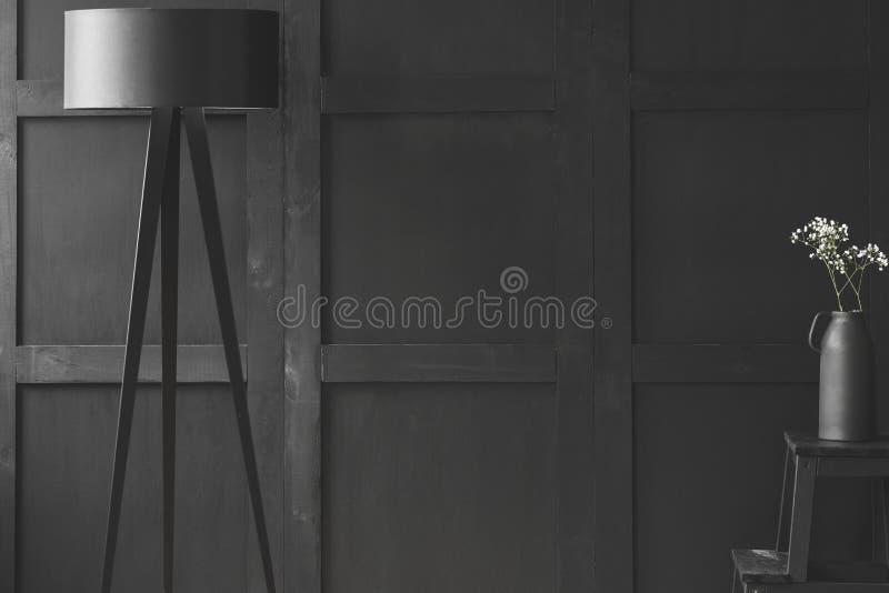 Zwarte lamp dichtbij witte bloemen op kruk in éénkleurige woonkamer i stock fotografie