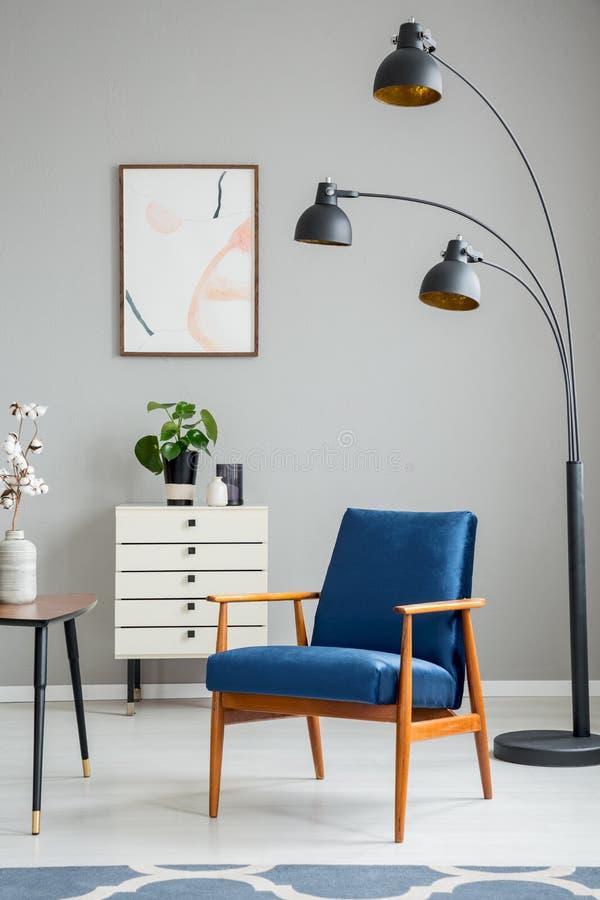 Zwarte lamp naast blauwe houten leunstoel in grijs flatbinnenland met affiche en installatie Echte foto royalty-vrije stock afbeeldingen