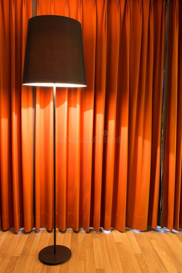 Zwarte lamp op tribune en rood gordijn stock fotografie