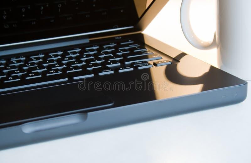 Zwarte laptop en witte mok stock foto