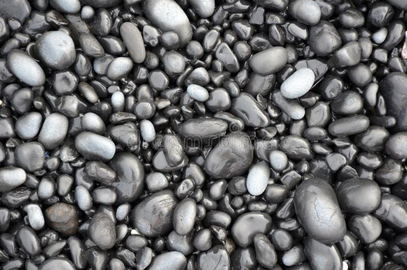 Zwarte lavakiezelstenen op strand royalty-vrije stock afbeeldingen