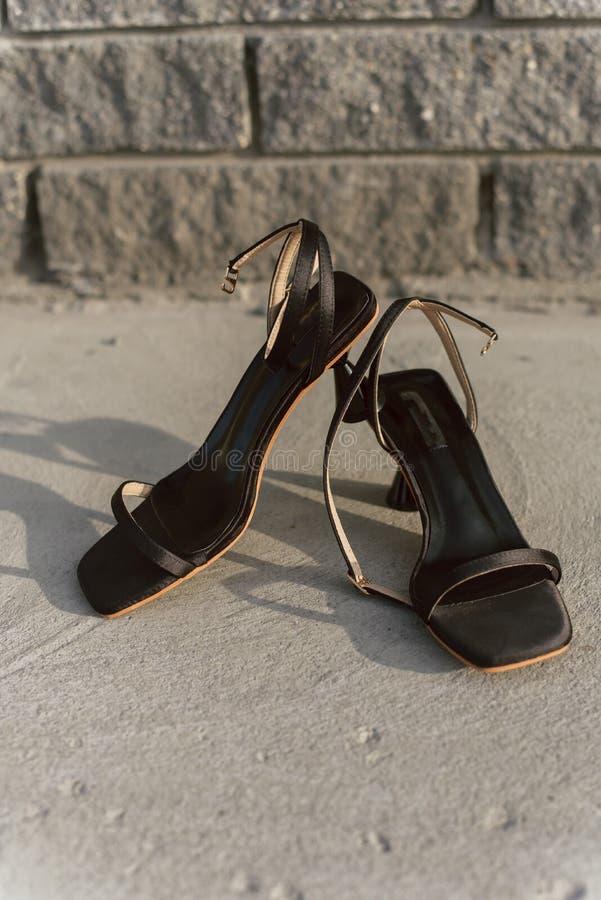 Zwarte leer open sandals met hielen bevinden zich op het asfalt in de zon De schoenen van vrouwen met gespen zonder iedereen royalty-vrije stock afbeeldingen