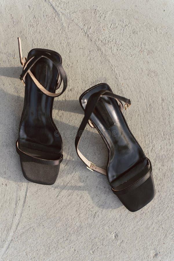 Zwarte leer open sandals met hielen bevinden zich op het asfalt in de zon De schoenen van vrouwen `s Verticale foto van modieus e stock fotografie