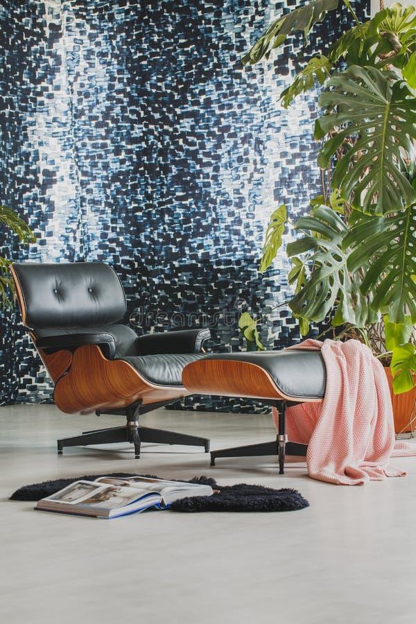 Zwarte leerstoel en kruk stock foto