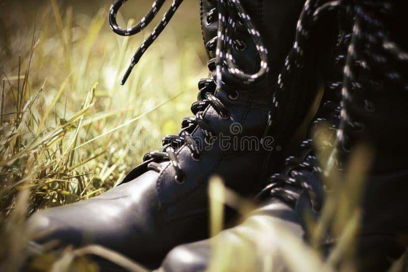 Zwarte leger hoge laarzen die zich in het gras bevinden royalty-vrije stock afbeeldingen