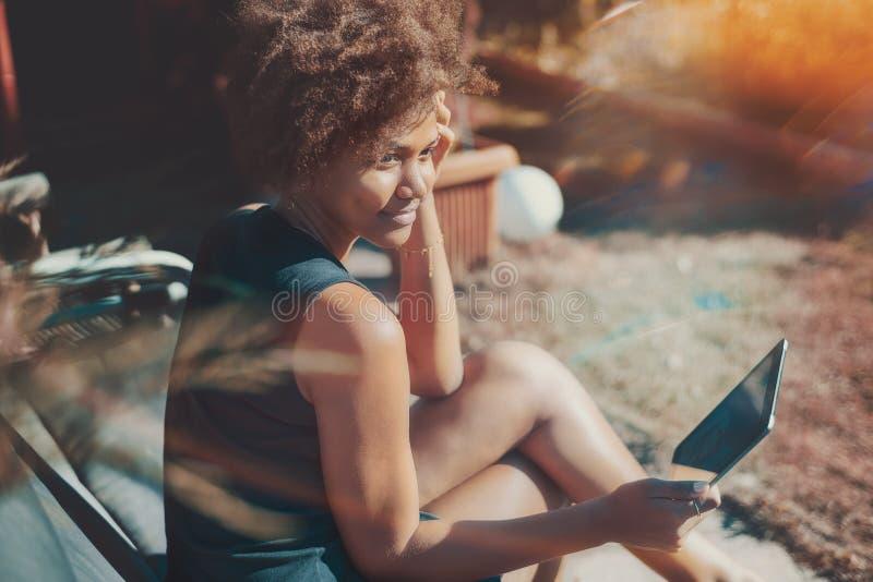 Zwarte leuke meisjeszitting in openlucht met digitale tablet in handen royalty-vrije stock foto's