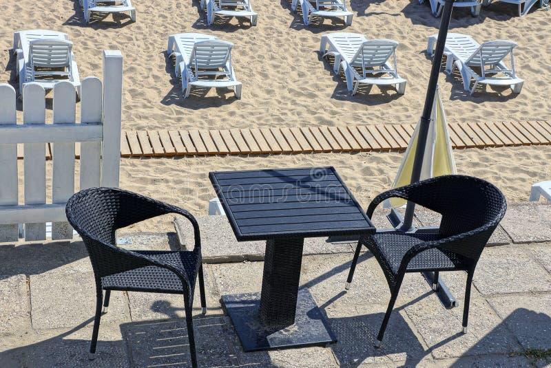 Zwarte lijst en stoelen op het restaurantgebied en plastic witte sunbeds in het zand op het strand stock foto's