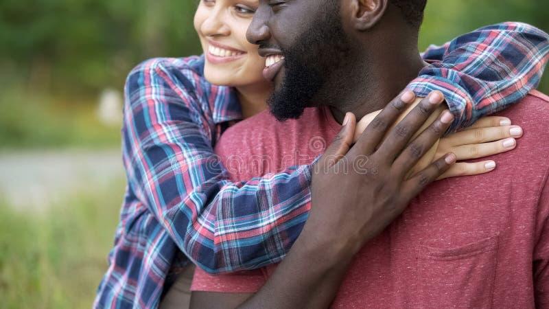 Zwarte man en gemengde rasvrouw die teder, gelukkige mensen die samen glimlachen koesteren stock foto