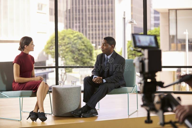 Zwarte man en witte vrouw die op reeks een TV-gesprek filmen royalty-vrije stock foto