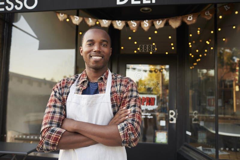 Zwarte mannelijke bedrijfseigenaar die zich buiten koffiewinkel bevinden stock afbeeldingen