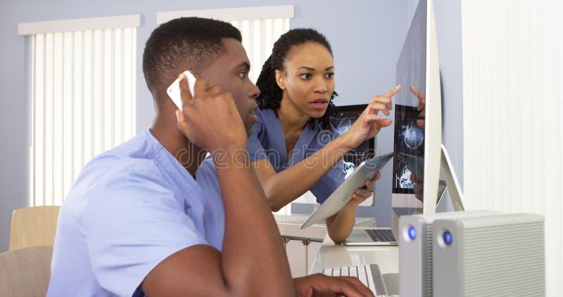 Zwarte medische specialisten die computer met behulp van om informatie samen te herzien stock foto's
