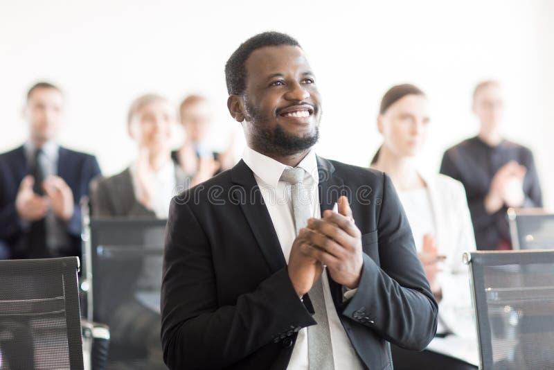 Zwarte mens die in conferentiezaal slaan stock fotografie