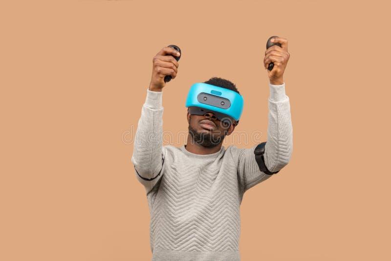 Zwarte mens die 3d vrglazen dragen, spelend videospelletje, die bedieningshendel in handen houden royalty-vrije stock foto's