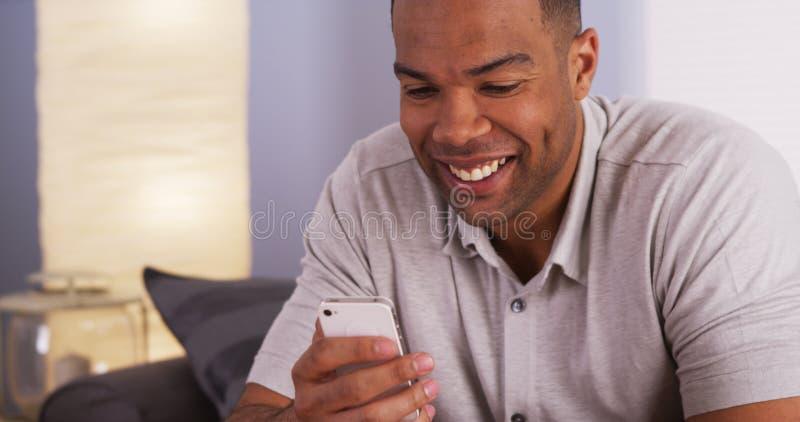 Zwarte mens die en op smartphone glimlachen texting royalty-vrije stock fotografie