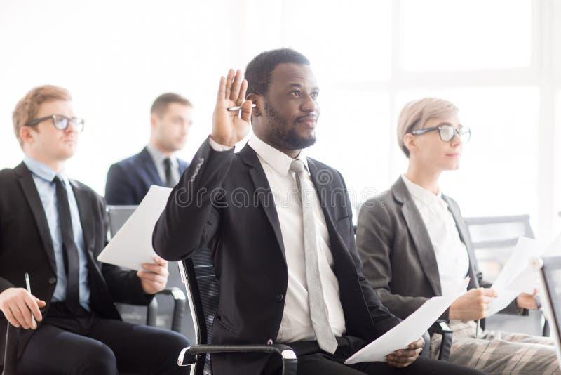 Zwarte mens die hand op commerciële vergadering opheffen royalty-vrije stock afbeelding