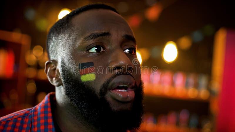 Zwarte mens die met geschilderde Duitse vlag zich op aankondiging van resultaten verheugen royalty-vrije stock afbeeldingen