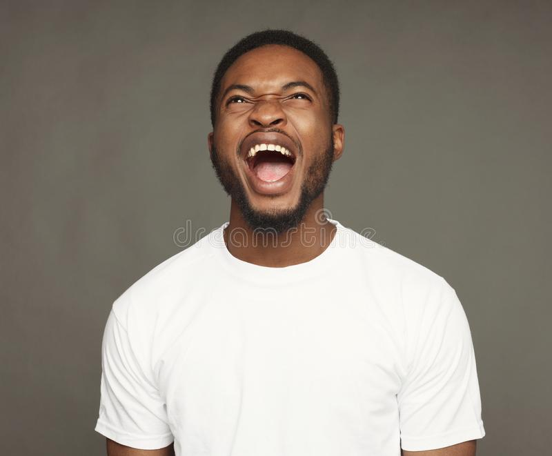 Zwarte mens die woede, woedend voelen uitdrukken, het schreeuwen stock foto's