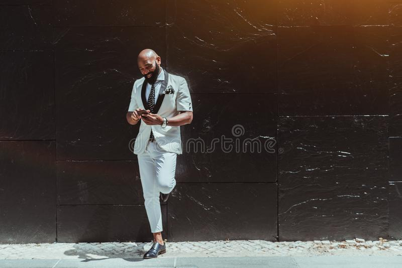 Zwarte mens met smartphone dichtbij muur royalty-vrije stock fotografie