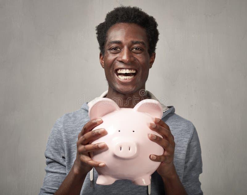 Zwarte mens met spaarvarken royalty-vrije stock fotografie