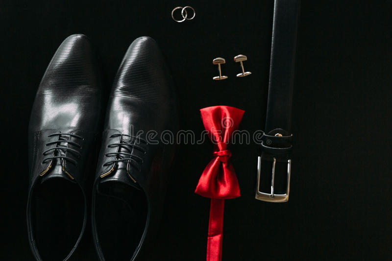 Zwarte mensen` s schoenen, cufflinks, trouwringen, een zwart band en a stock foto's