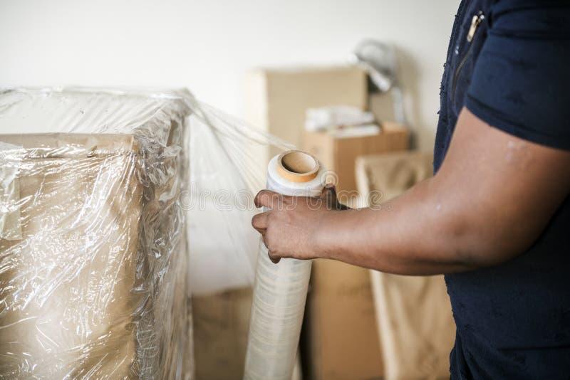 Zwarte mensenverpakking op meubilair stock foto