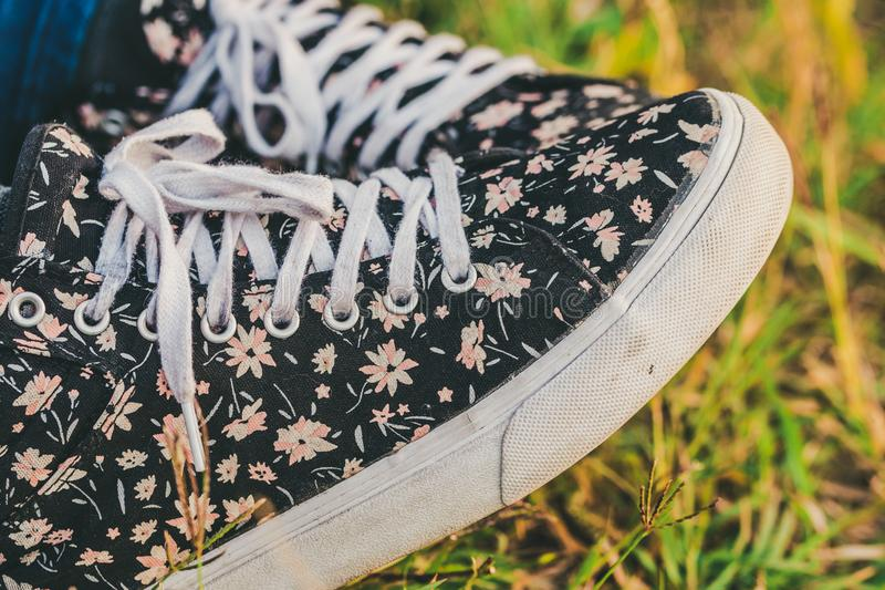 Zwarte met bloementennisschoenen op gras royalty-vrije stock fotografie