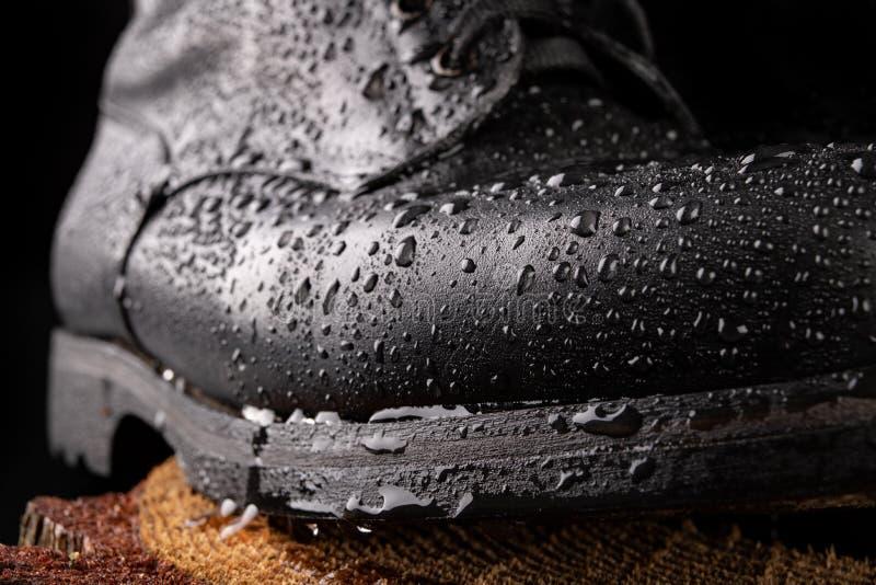 Zwarte militaire laarzen en regendalingen Goed-bewaarde oude laarzen voor militairen stock fotografie