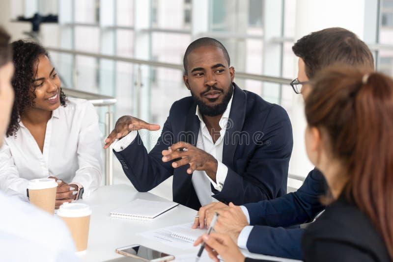 Zwarte millennial werkgever die collectief team leiden tijdens briefing in bestuurskamer royalty-vrije stock afbeelding