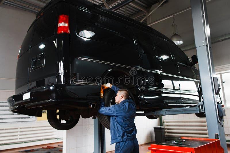 Zwarte minibus op reparatie in garage stock afbeelding