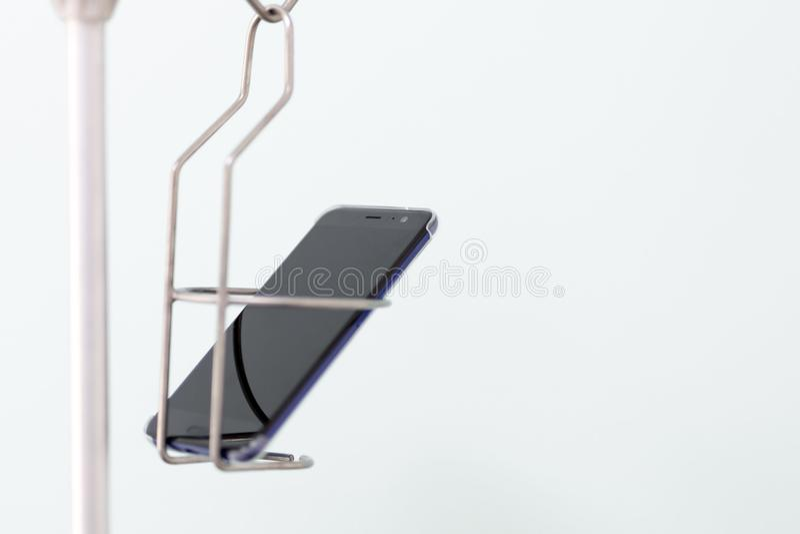 Zwarte moderne smartphone in een medische druppelbuisjehouder Telefoon en het sociale concept van de netwerkverslaving royalty-vrije stock afbeeldingen