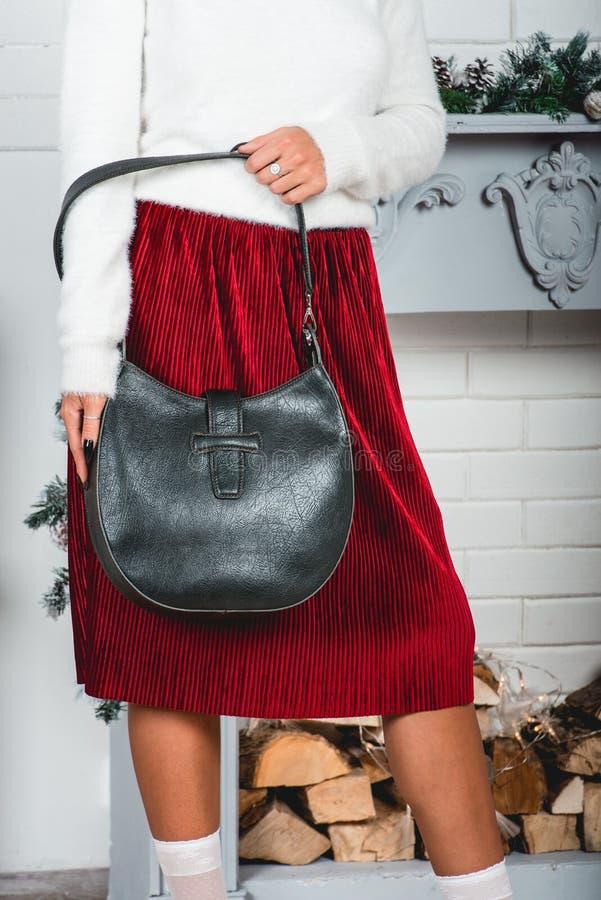 Zwarte modieuze handtas in handen van schitterend jong wijfje in een rode rok en witte trui op verfraaide Kerstmis stock afbeelding