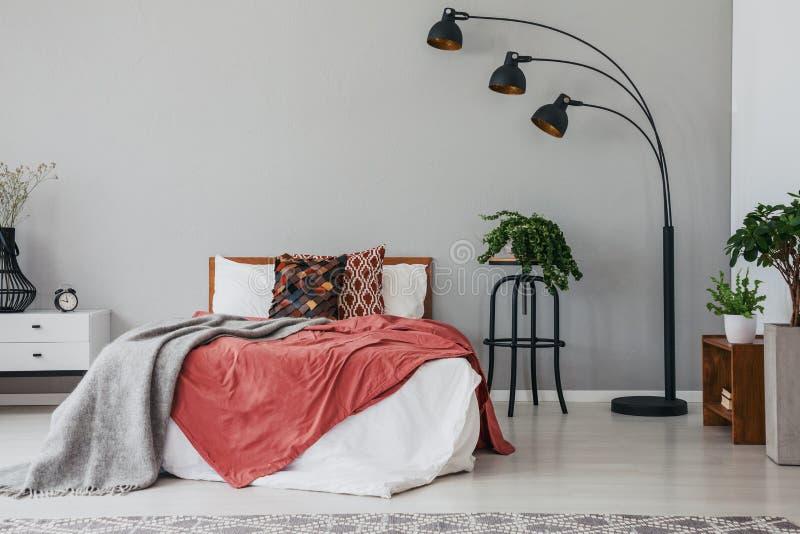 Zwarte modieuze lamp in elegant slaapkamerbinnenland met comfortabele tweepersoonsbed, installaties, en bedlijst stock fotografie