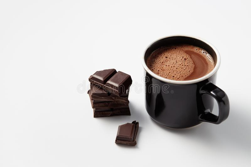 Zwarte mok met hete die chocolade met brokken van donkere chocolat wordt gediend stock foto