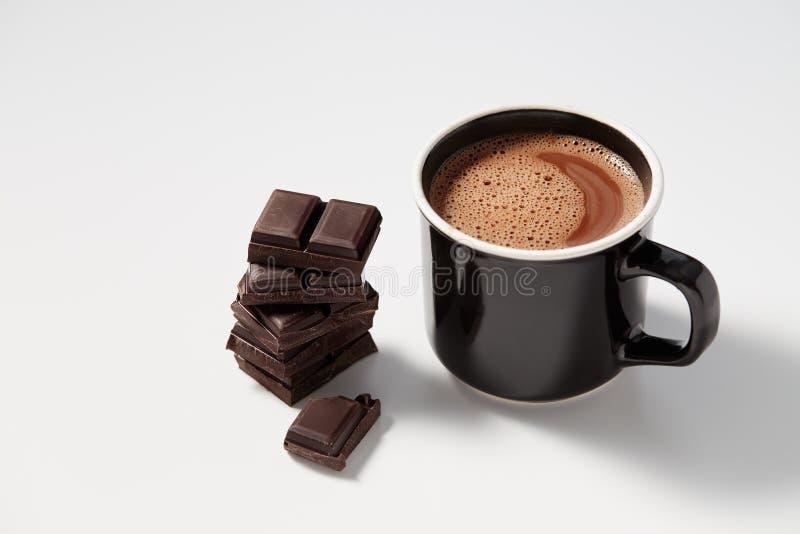 Zwarte mok met hete die chocolade met brokken van donkere chocolat wordt gediend royalty-vrije stock foto's
