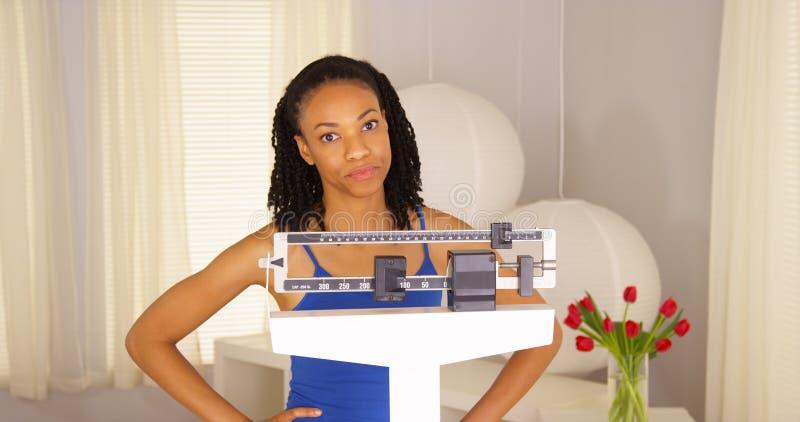 Zwarte na het controleren van gewicht op schalen wordt teleurgesteld die stock fotografie