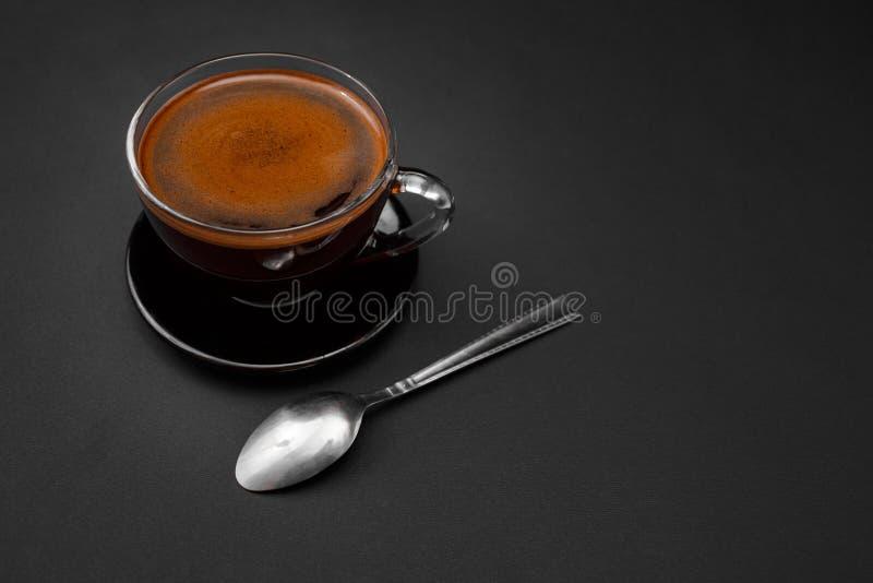 Zwarte, natuurlijke, geurige koffie in de transparante kop op een zwarte achtergrond royalty-vrije stock fotografie