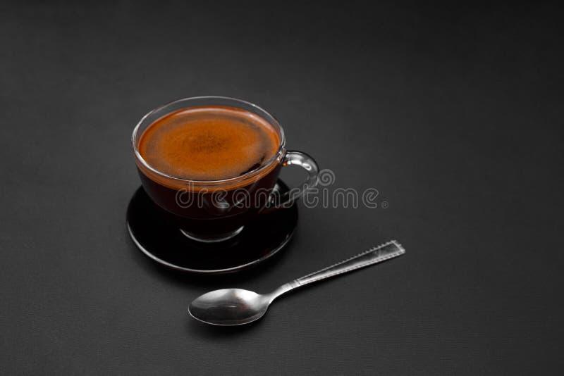 Zwarte, natuurlijke, geurige koffie in de transparante kop op een zwarte achtergrond stock afbeeldingen